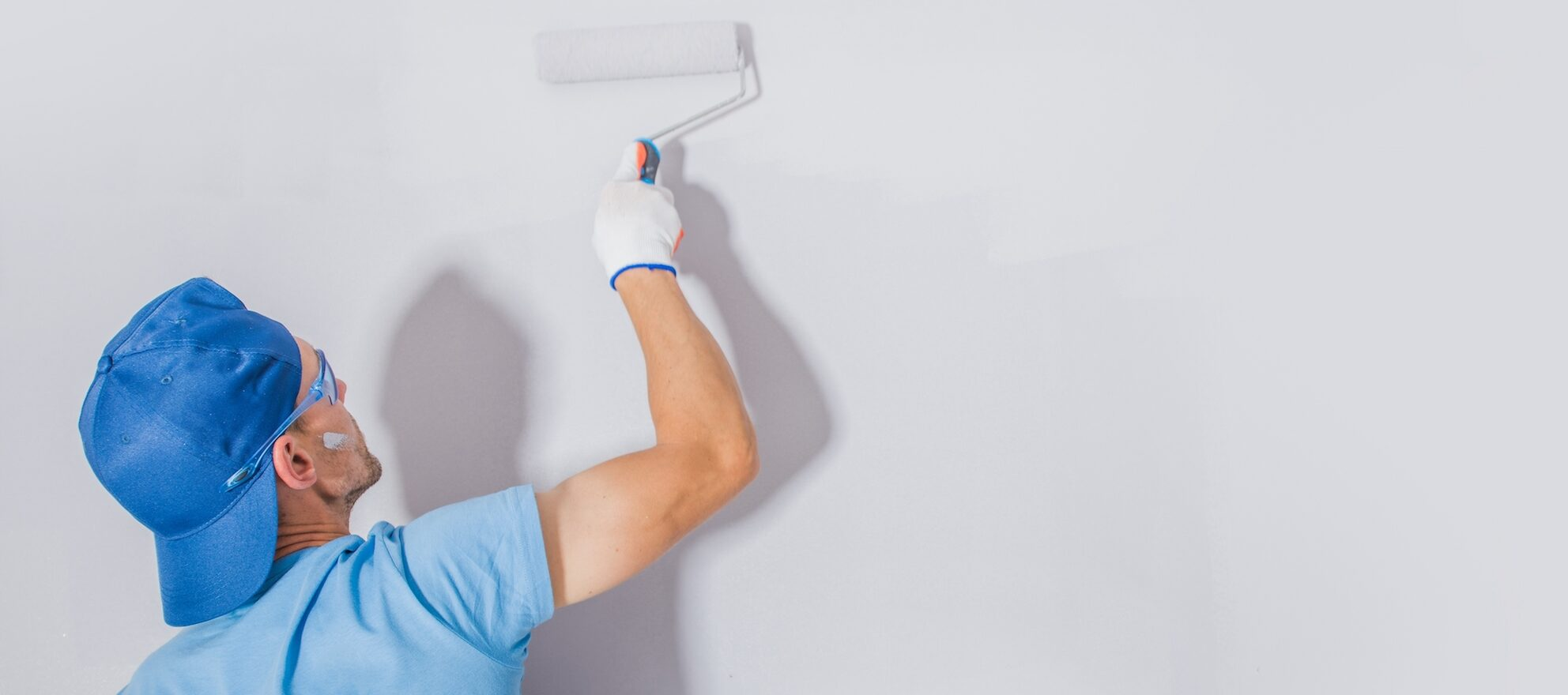 A man painting a wall with a roller